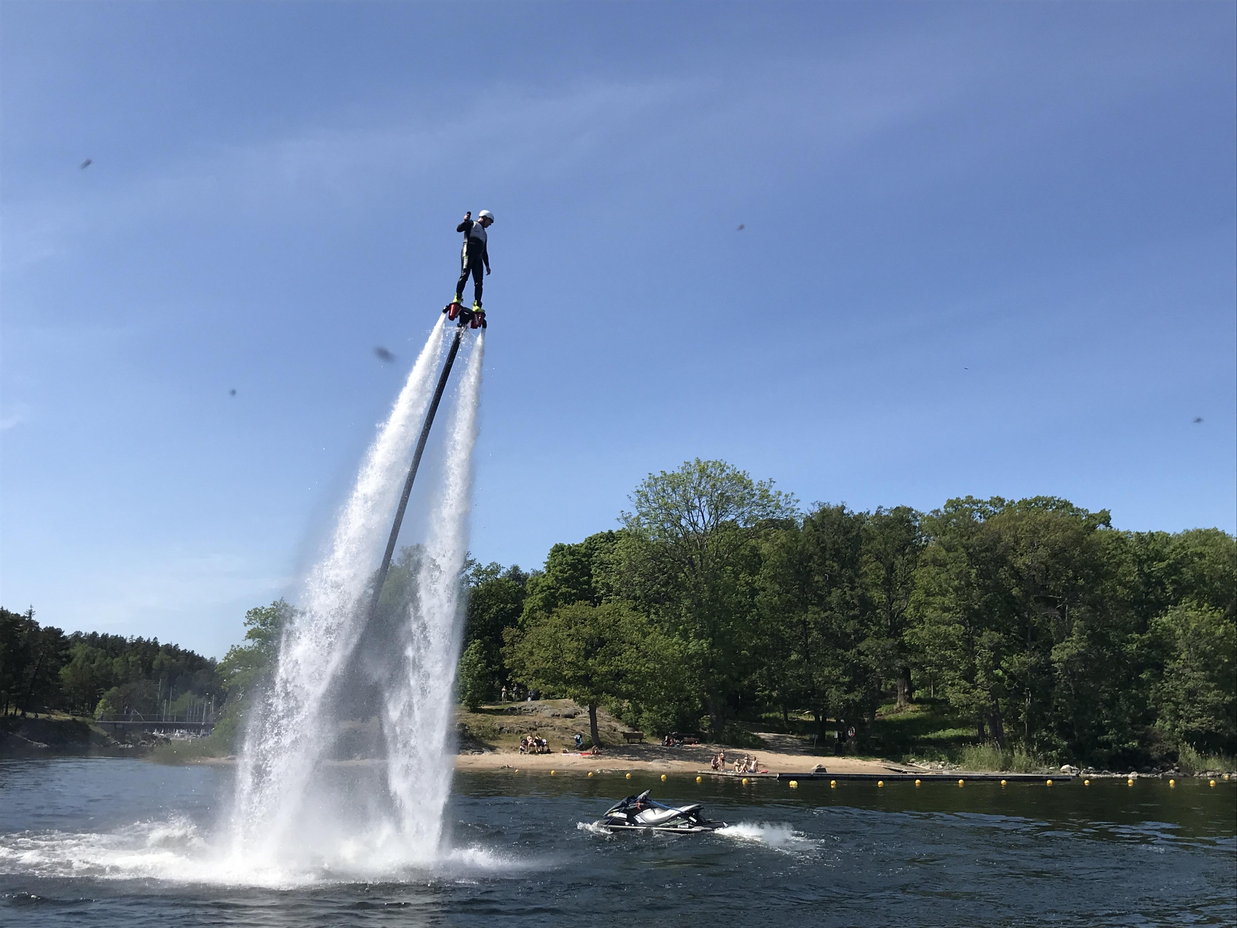 Person som flyger högt med flyboardbräda mot blå himmel